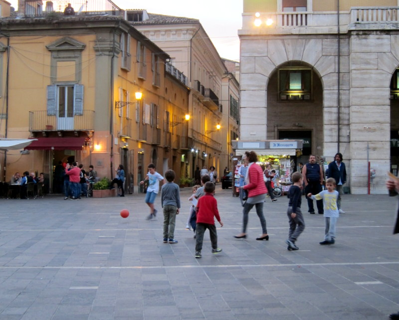 The main piazza - as the evening dims the light two or three different groups of boys played soccer amidst pedestrian traffic